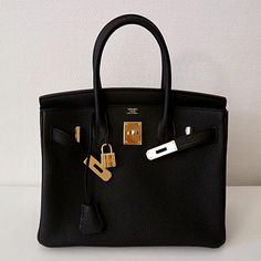 STYLE DETAILS Hermes Birkin in Black leather with gold hardware. This Birkin has tonal stitching, a front toggle closure, a clochette with lock and two keys, and double rolled handles. Hermes Handbags, Fashion Handbags, Fall Handbags, Fossil Handbags, Cheap Handbags, Cheap Bags, Luxury Bags, Luxury Handbags, Luxury Purses