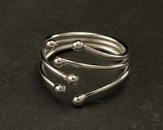 This sterling silver ring was designed around a simple curving line which wraps around the finger. The ring is accentuated with little silver balls. This ring was designed for comfort and is slightly adjustable for the perfect fit. Sure to be your new favorite everyday ring!  In stock ring sizes: 5, 6, 6.5, 7, 7.5, 8, 8.5 (Ready to ship) All other sizes made to order (ships in 5 days)  The ring will arrive gift-wrapped in a jewelry box tied with ribbon. Domestic Shipping includes Delivery…