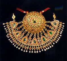 India | Head ornament; 20k gold, set with cabochon cut rubies, emeralds, table cut diamonds and suspended Basra pearls | Rajasthan; 19th century | This head ornament was worn on the side of the head, the fringe is hanging down covering one side of the forehead. This type of jewellery is part of traditional jewellery