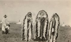 circa 1910 Notes Three Blackfoot Indians, wearing long feather war bonnets, stand with backs toward camera. Unidentified man and child stand left. Tipis in background . Native American Photography, Native American Photos, Native American Tribes, Blackfoot Indian, Montana, Great Lakes Region, Tribal People, Dancing In The Rain, First Nations