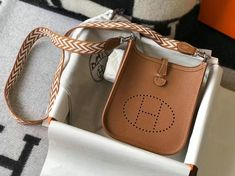 With our beautiful Hermes replicas, you can acquire a bag that contains all of these attributes for half the price. Our company offers the same quality and luxury that you'd expect from Hermes. However, our prices are significantly lower. When you show off your brand-new replica Hermes bag, you can guarantee that nobody will be able to spot the difference. Hermes Evelyn Bag, Hermes Orange, Hermes Online, Go Bags, Shop Up, Electric Blue, Bag Sale, Red Roses, Messenger Bag