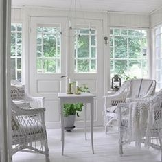 White Scandinavian sun room with wicker chairs By Asr