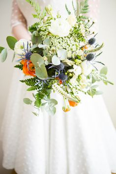 """Free Form"" Wedding Bouquet With: Blue Eryngium Thistle, Orange Ranunculus, White Ranunculus, White Queen Anne's Lace, White Astrantia, White Veronica, Green Silver Dollar Eucalyptus, Green Fern, Green Sword Fern + Additional Greenery/Foliage"