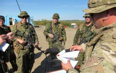 20 August 2012 Tsiigehtchic, Northwest Territories, Canada A member of the RCMP Emergency Response Team gives orders to Canadian Forces (CF) soldiers from the Third Battalion, Princess Patricia's Canadian Light Infantry (3 PPCLI), Immediate Response Unit, during a CF assistance to RCMP scenario in Tsiigehtchic, NT, on Operation NANOOK 2012.