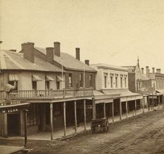 Hindley Street, Adelaide, looking west from a point opposite Gilbert Place, on a wet day. On the left, a large model of an emu stands above the verandah of  'Emu House'. J.W.Egan's store is on the ground floor. T. Ide is the licensee of the Blenheim Hotel, on the Gilbert Place corner. The roof appears to be shingle, there is turned wood balustrading on the balcony and cheerful striped window awnings. Later [1882] this hotel became the Tattersalls, and is still extant in 2006.