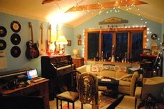 Soft furniture dampens sounds. Records & guitar on wall creates mood. Desk lends multi-purpose to small room.
