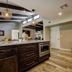 The cabinets in this kitchen look amazing. I like how dark the wood is, and how you can still see the wood grain through the stain color. The width of the cabinets also seems like it would be helpful when it comes to storage.