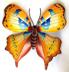"""Butterfly Metal Art Wall Hanging - Tropical Home Decor - Hand Painted Steel Drum - 18"""" x 21""""  Painted metal garden decor - Butterfly wall art - Tropical décor, Hand painted butterfly, Tropical art, Butterfly wall hanging, Haitian metal art  Outstanding gold and blue hand painted metal butterfly wall decor. Wonderful for your indoor or outdoor decorating.    Handcrafted from a recycled steel drum at our workshop in Haiti.   Hand painted metal butterfly measures 18"""" x 21""""."""