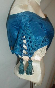"""1860s evening bodice, ebay seller: fiddybee; museum de-accessioned; net lace under sleeve; cap sleeve has tassel trimmed lacing & decorated with printed silk ribbon with circles of blue chenille; under sleeve has pink ribbon insert; lined in cotton, back hook & eye closure; no underarm discoloration; bust: 32""""; waist: 24"""""""