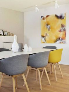 danish interior design dining table with gray chairs and yellow art