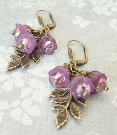 SOLD! Created with tiny lucite bell flowers, custom tinted in a deep purple, Topped with bronze tone filigree, sparkling lilac crystal glass and dainty flower spacers. Clustered together over a bronze leaf charm   $19.00