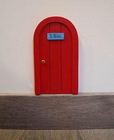 Puerta roja para el ratón Pérez. Con forma redonda, como las típicas ratoneras. Esta puerta solo puede ser abierta por la magia del Ratoncito Pérez. Ilustrada imitando la veta de la madera. Un puerta para el ratoncito Pérez con diseño original de La iluminista.