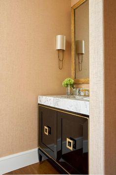 Gold grasscloth wallpaper covers the walls of this stunning bathroom lit by gold sconces flanking a Black Powder Room, Tiny Powder Rooms, Gold Grasscloth Wallpaper, Bathroom Wallpaper, Powder Room Vanity, Bath Powder, Module Design, Contemporary Bathroom Designs, Contemporary Design