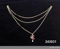HalssmyckeHängsmycke i form av bokstaven C med två berlocker - en blå Ceylonsafir och en vit barockpärla - Hänger på en guldkedja av pansarlänk som består av tre kedjor kopplade till ett smalt lås. Kedjan inte ursprunglig i sin modell troligtvis ändrad under 1700- eller 1800-talet då också det nuvarande låset tillkommit. Smycket är av guld belagd med röd emalj. Ornament av guld runt bokstavens yttre kant delvis belagda med grön, svart och ljusblå emalj. Det övre ornamentet avslutas med en…