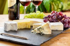 Cheese board tray with Brie, Gouda, sharp cheddar, Chèvre and Blue cheese as well as grapes, strawberries, sliced apple, olives, sweet preserves, honey, almonds, sliced baguette, bread sticks and crackers in all different shapes and sizes.
