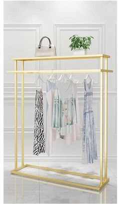 Golden clothes shelf clothing store in the island frame double sided women's clothing store bag display rack floor double row. Hanging Clothes Racks, Clothes Shelves, Clothing Store Interior, Clothing Store Displays, Bag Display, Display Shelves, Womens Clothing Stores, Women's Clothing, Clothes For Women