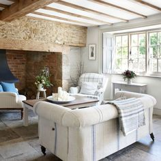 Living room  A cool Scandinavian palette offsets the mellow stone of the inglenook fireplace in this bright and breezy living room. The stone floor has been left uncovered, revealing its beauty and the house's rustic credentials. The antique Chesterfield sofa has been covered in vintage Hungarian grain sacks and the throw is also a vintage textile.   Similar sofa Sofa.com Similar console table Marks & Spencer  Read more at…