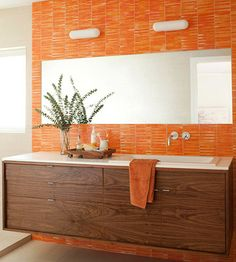 An orange tile accent wall lets the color do the talking in this vibrant bathroom. A large frameless mirror balances the bold hue and adds to the horizontal effect of the space. Orange Bathrooms Designs, Bathroom Vanity Designs, Bathroom Wall Decor, Bathroom Colors, Modern Bathroom, Colorful Bathroom, Bathroom Mirrors, Wood Bathroom, Decoration Inspiration