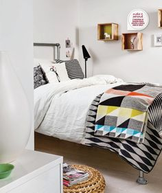 Geometric bedspread and industrial DIY looking bed frame.
