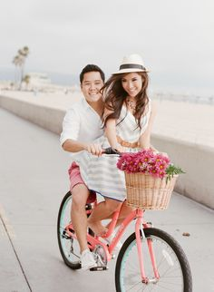 Couple on their pink bicycle with basket of flowers during their engagement session.