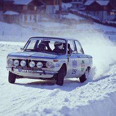 Vintage racing BMW in snow.