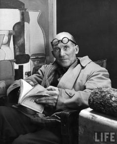 [FA] : Architect Le Corbusier sitting in chair & holding book in hands-- Paris France 1965.