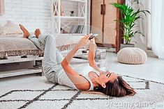 Woman laying on floor in livingroom text messaging on cell phone Text Messaging, Connection, Messages, Flooring, Stock Photos, Fresh, Living Room, Female, Woman