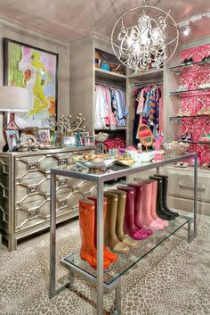 Pink and gray closet features gray built-ins fitted with stacked clothes rails flanking a Global Views Greenbrier Chest facing a metal and glass closet island lined with rubber rain boots, Wellies, illuminated by a sphere pendant, Crystorama Solaris Chandelier, alongside leopard print carpeting.