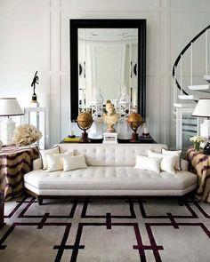 Pablo Paniagua living room--bold white and raspberry color palette, tufted sofa, skirted side table, geometric rug