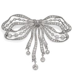 A BELLE EPOQUE DIAMOND, PLATINUM AND 9K GOLD BROOCH, CIRCA 1910. Designed as a ribbon bow set with old cut diamonds, the four articulated tassels set with old cut diamonds, mounted in platinum and 9k gold. #BelleÉpoque #brooch