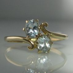 A pretty vintage ice blue gemstone ring set in gold. The ring has a split band with a swirl detail encasing two gemstones. Ring size: T (This ring can be resized if required). Vintage Jewellery, Vintage Rings, Unique Vintage, Blue Gemstones, Gemstone Colors, Engagement Jewelry, Diamond Engagement Rings, Diamond Rings, Gemstone Rings