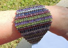 This is an incredible runway bracelet. It is covered with gemstones: amethysts, peridots, white sapphires, pink sapphires, blue sapphires and