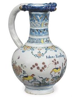 AN ENGLISH DELFT POLYCHROME INSCRIBED AND DATED PUZZLE-JUG 1742, PROBABLY LAMBETH Of globular form with pierced waisted neck, hollow handle and top rim with three spouts, the body painted in a vibrant Kakiemon palette with birds perched among prunus and bamboo issuing from hedges and a fence, with the name Iohn:Keeling. above, the shoulder with elaborate lappets and strapwork with pendant swags of flowers and scrolls, the neck with alternate bands of diaper and pierced ornament,
