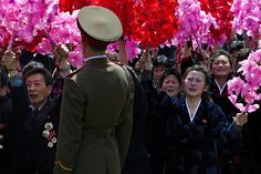 North Korean civilians, some weeping, wave flowers as they look up at Kim Jong Un, unseen, at the end of the military parade on April 15, 2012.