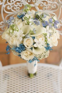 Bride's ivory white bouquet with a touch of blue, dimensions, ivory roses, white calla lilies, white stock flowers, light blue delphiniums, blue baby's breath, stephanotis accented with crystals/jewels, bridal bouquet blue, bridal bouquet