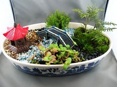 this dish garden looks like an outside replication  includes pepples looks like trees and includes a bridge.