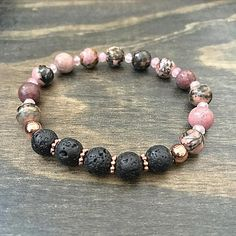 ESSENTIAL OIL DIFFUSER BRACELET This gemstone stretch bracelet is made with Rhodonite, pink dyed Malaysian Jade and lava stone beads for diffusing essential oils. Ive added accents of rose gold metal accents to compliment the pink in the Rhodonite beads. Pretty enough to wear alone,