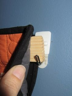 """How to Hang a Quilt:  cut baseboard (1 1/4"""" x 1/4"""" thick) to length, insert it in the sleeve (make sure sleeve is an inch or two short) and hang.  Use Command hooks that will hold 2-3 lbs."""