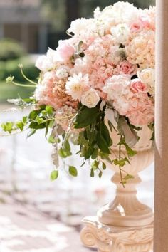 Urns filled with pink hydrangeas, pink roses, white spray roses with hints of seeded eucalyptus and dusty miller dripping from the base will sit at the base of the stairs on either side of the stairs.