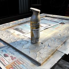 A faux metallic mirror frame made by mixing crack filler and wood glue, and then pressing it down with a wooden spoon