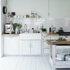 Painted wood floor / distressed cabinet / farmhouse sink / subway tile