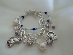 Simple Stack Charm Bracelet: Designed and handmade by Els, this is a memory wire seed bead bracelet attched to a cute charm bracelet in a stack fashion.  Pretty bicone dangles and cute wire wrapped pearls, with added fashion charms....