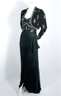 Beaded silk velvet evening ensemble, c.1940. I love the haunting beauty of the deep rich green hue. The strapless dress features a softly draped skirt with a provocatively deep slit. The unlined bolero style jacket, open in front, reveals the low-cut neckline of the dress. The jacket and dress bodice are embellished with sparkling bouquets of rhinestones and clear crystal beads. What a dramatic and sophisticated fashion statement!