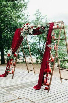 Arche de cérémonie laïque avec deux échelles, des voilages rouges et des fleurs