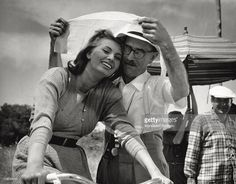 The Italian actress Sophia Loren (Sofia Villani Scicolone) and the Italian director Mario Soldati screening themselves from the sun with a scarf on the set of the film The River Girl. Italy, 1954