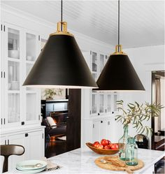 Large black and gold pendant lights over white marble kitchen island