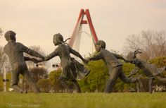 """""""Crack the Whip"""" by Jo Saylors sculpture in Columbus, Indiana with the Robert N. Stewart Bridge in the background. Photo by Shannon Malanoski"""