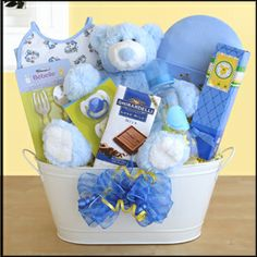"""New Arrival Boy $94.99  A wonderful way to say """"Welcome to the world""""! This lovable plush bear is surrounded by treats for baby and mom alike .GIft Basket includes: Baby Bib, Mittens,Hat,Washcloth,Brush,Comb,Vest, Bottle,Pacifier,Baby Fork Spoon,Baby Shampoo, Powder and Lotion, Johnson and Johnson's Baby Shampoo, Powder and Lotion,www Ghirardelli Bar and Cookies. just adorable!"""