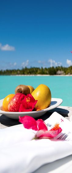beach inspired brunch setting with organic fruits at an eco-friendly resort.