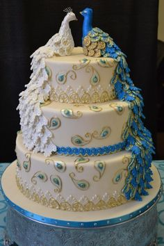 Romantic peacock wedding cake! Bride is white...groom is blue.   Would be great if two guys were married since both peacocks are male.